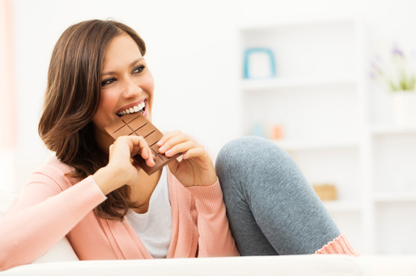 happy-woman-taking-bite-of-chocolate-bar